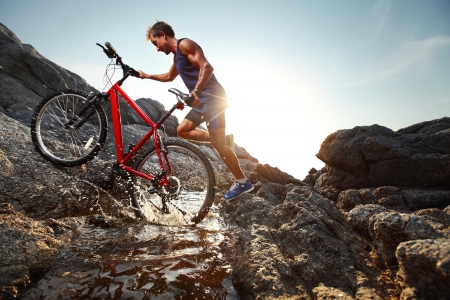 Young athlete crossing water barrier with bicycle Stock Photo - 19872954