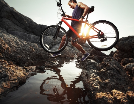 mountain pass: Young athlete crossing rocky terrain with bicycle in his hands