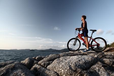 valley view: Giovane atleta in piedi sulla cima di una montagna con la bici e godersi la vista sulla valle Archivio Fotografico