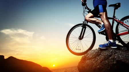 cliff edge: Young athlete standing on a rock with bicycle