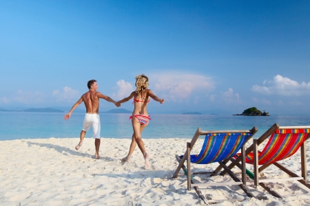 Young happy couple having fun on a tropical resorts white beach photo