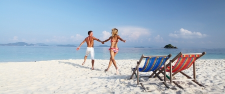 wide wet: Young happy couple having fun on a tropical resorts white beach Stock Photo