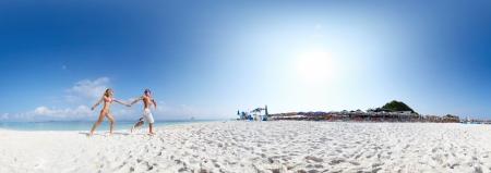 晴れた日で、熱帯の島の砂浜のビーチで実行されている幸せなカップルとパノラマ