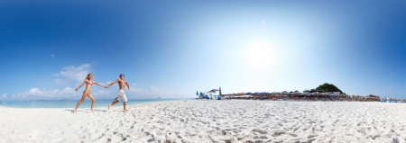 Panorama with young happy couple running on a sandy beach of tropical island at sunny day photo