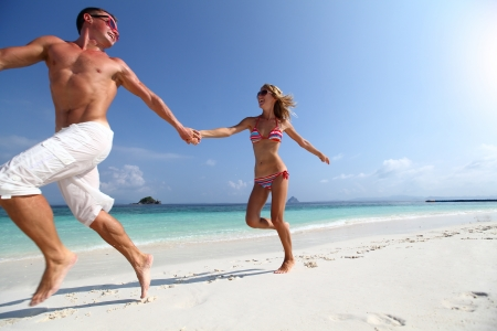 active couple: Active couple running on a white sandy beach with blue sky on the background Stock Photo