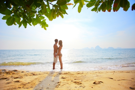 Young couple standing on a sandy beach photo