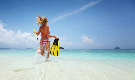 into: Young lady running into tropical sea with snorkeling equipment at sunny day