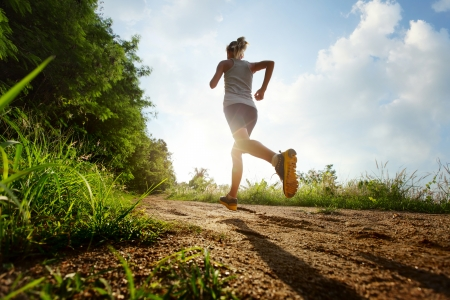 extreme sport: Young lady running on a rural road during sunset