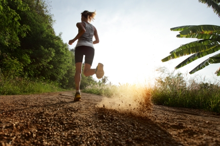 athlete woman: Young lady running on a rural road during sunset