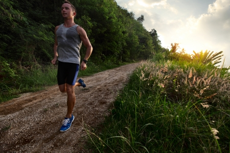 perspiration: Young man with wet singlet running on a rural road during sunset Stock Photo