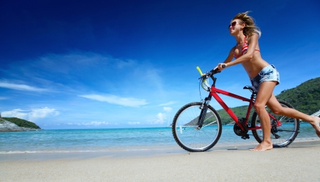 Young smiling lady running with bicycle on a sandy tropical coast