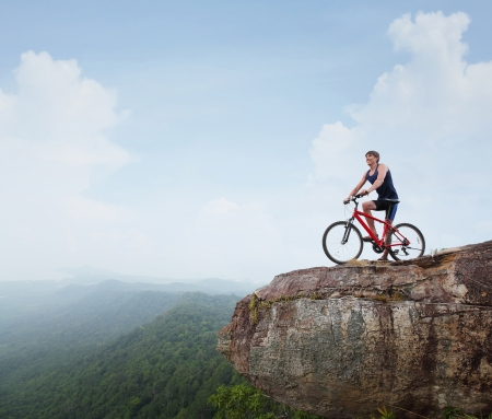 mountain bicycle: Young athlete standing on top of a mountain with bicycle and enjoying valley view