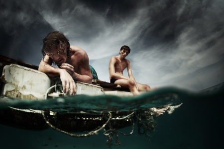 Two men floating in a sea with sad faces and wounds on a body