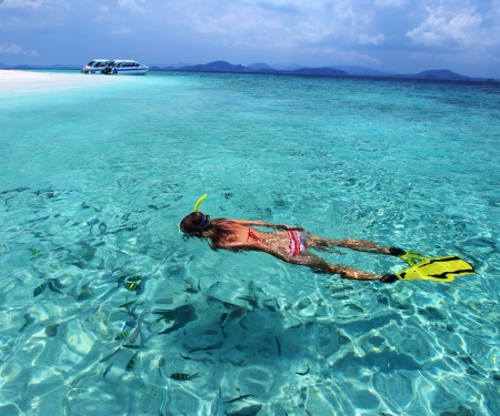 bottom of sea: Young lady snorkeling in a turquoise tropical sea by a white sandy beach