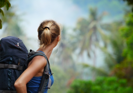 turn back: Young tourist with backpack walking in tropical forest Stock Photo