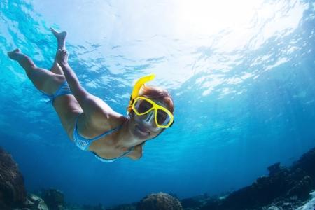 corales marinos: Lanzamiento de un submarino de buceo joven y hacer buceo de superficie en un mar tropical