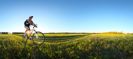 countryside: Young man cycling on a rural road through green spring meadow during sunset