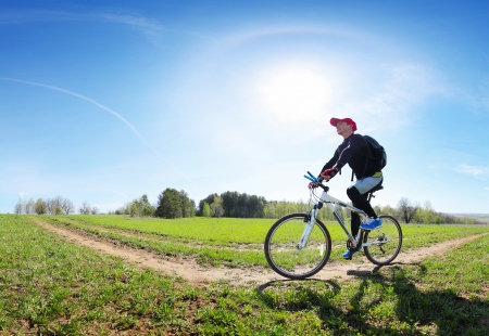 space weather tire: Young man cycling on a rural road through green spring meadow at sunny day Stock Photo