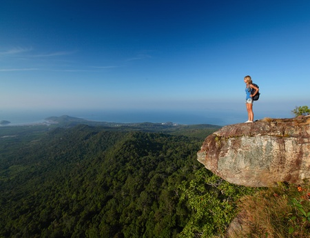 edge of cliff: Lady with backpack standing by an edge of a cliff and enjoying valley view Stock Photo