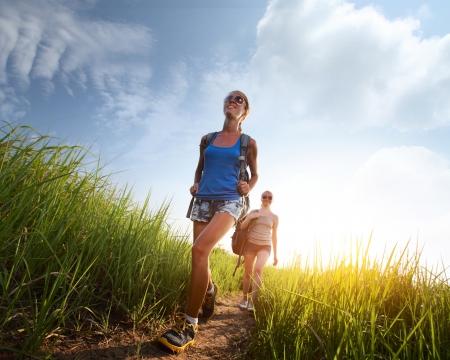 caminando: Dos jovencitas caminando con mochilas a trav�s de vegetaci�n exuberante prado Foto de archivo