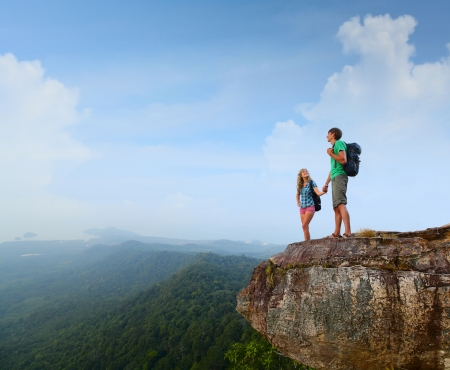 2 つのハイカー、山の頂上に立っていると、谷の眺めを楽しむ