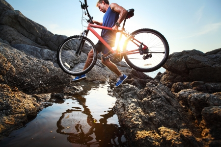 mountain bike: Young athlete crossing rocky terrain with bicycle in his hands