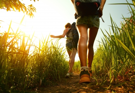 adventure sports: Two young ladies walking with backpacks through green lush meadow