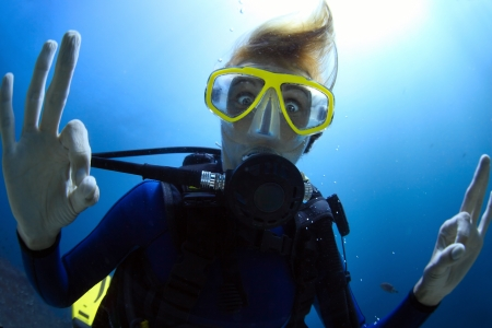 Crazy diver showing ok signal with bulging eyes photo