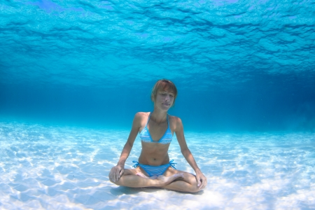 yogic: Young woman holding a breath and relaxing on a sandy bottom in a yogic lotus position