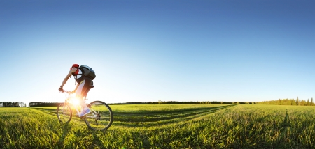 Jonge man fietsen op een landweg door groene lente weide tijdens zonsondergang