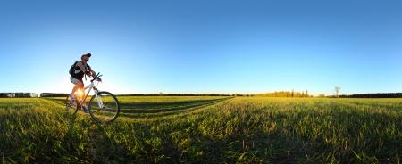 若い男が日没時にグリーン春の牧草地を通して農村部の道路上の自転車