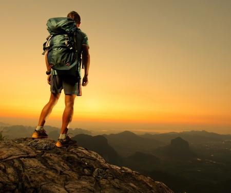 aventura: Caminante con mochila de pie en la cima de una montaña y disfrutar de la salida del sol