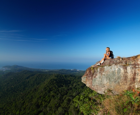 cliff edge: Lady with backpack sitting on an edge of a cliff and enjoying valley view Stock Photo