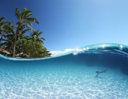 beneath the surface: Blue tropical clear sea with sandy bottom and green palm trees on a coast. Silhouette of a snorkeler at right corner