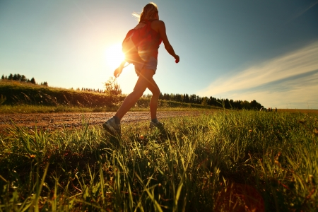woman freedom: Hiker with backpack walking on a gravel road