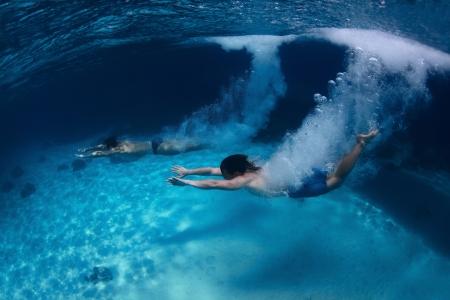 two stroke: Disparar bajo el agua de dos j�venes saltando en un mar transparente, con un mont�n de burbujas Foto de archivo