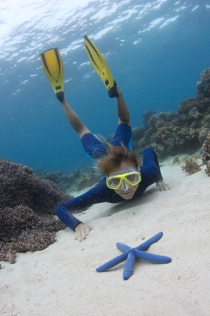 beneath the surface: Young lady diving on a breath hold and exploring sea bottom Stock Photo