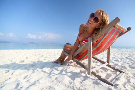 strandstoel: Jonge dame ontspannen in een stoel op een strand op zonnige dag