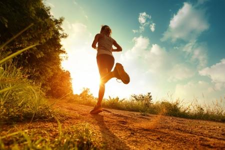 deportista: Señora joven que se ejecuta en un camino rural al atardecer