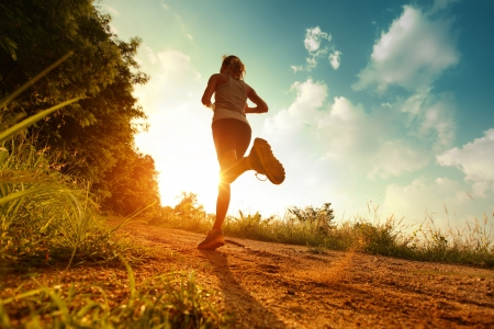athlete: Young lady running on a rural road during sunset