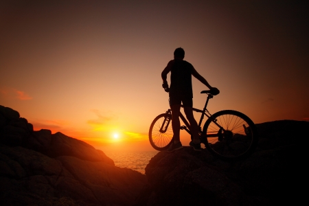 steep cliff: Silhouette of bicycle rider on a rock at sunset