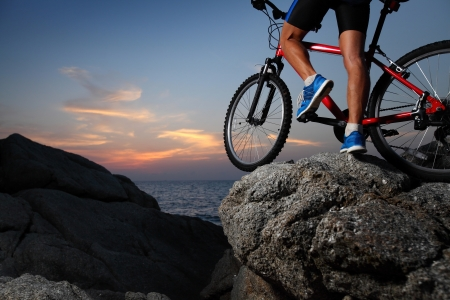 steep cliff: Bicycle rider standing on a rock at sunset Stock Photo