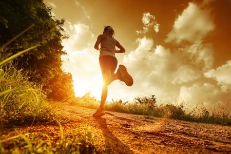 hacer footing: Se�ora joven que se ejecuta en un camino rural al atardecer