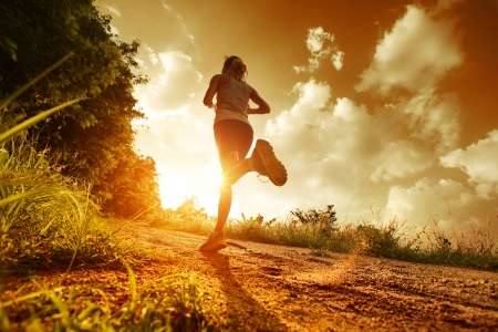 sportsman: Young lady running on a rural road during sunset