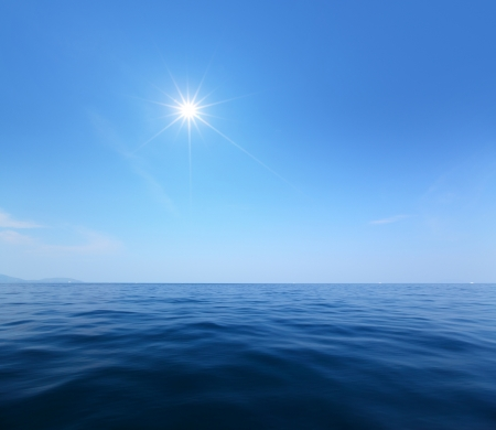 Calm tropical sea surface and blue sky with sun Stock Photo