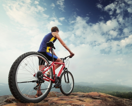 Young man standing with bicycle on top of a mountain photo