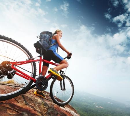 Turista femenino con la mochila y bicicleta disfrutando de vistas al valle desde la cima de una montaña