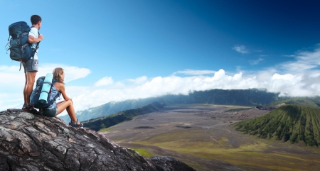 Two hikers with backpacks relaxing on top of a hill with valley view photo