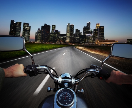 Driver riding motorcycle on an asphalt road at night towards big city photo