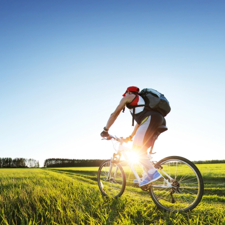 Jonge man fietsen op een landelijke weg door groene lente weide tijdens zonsondergang